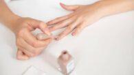 Young woman applying nail polish at home